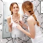 בחורה מתאפרת באמבטיה מול המראה ללא שום בעיה בזכות מפיג אדים למראה